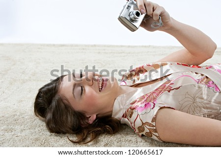 Young beautiful woman looking at a digital photo camera while laying down on a furry carpet at home against a white background, smiling. - stock photo