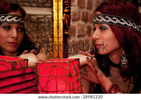 young beautiful woman looking herself in mirror - stock photo