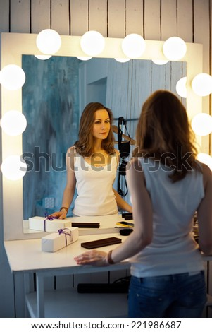 Young beautiful woman looking in the mirror - stock photo