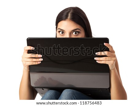 Young beautiful woman looking over a laptop against white background - stock photo