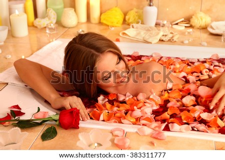 Young beautiful woman luxuriating with rose petals hot bath in spa saloon.  - stock photo