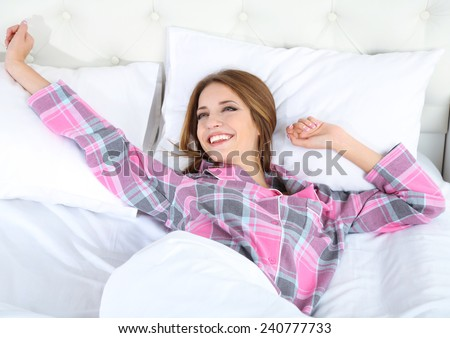 Young beautiful woman lying in bed - stock photo