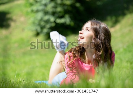 Young beautiful woman lying in grass and smiling - stock photo