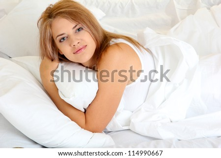 young beautiful woman lying on bed in bedroom - stock photo