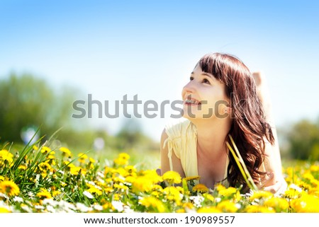 Young beautiful woman lying on grass full of spring flowers, looking happy at the sunny blue sky. Happiness, harmony, wellness, relaxation concepts. - stock photo