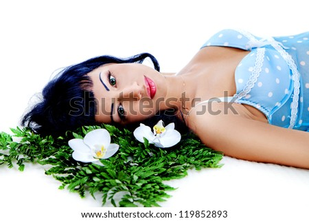Young beautiful woman lying on leaves with orchid flowers - stock photo