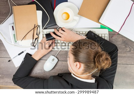 Young beautiful woman lying on the desktop. Fatigue in the workplace. Office modern life. Top view. Working hard - stock photo
