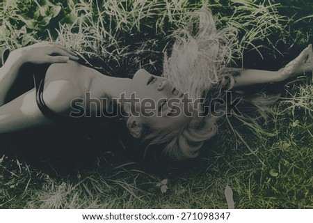 Young beautiful woman lying on the grass - stock photo