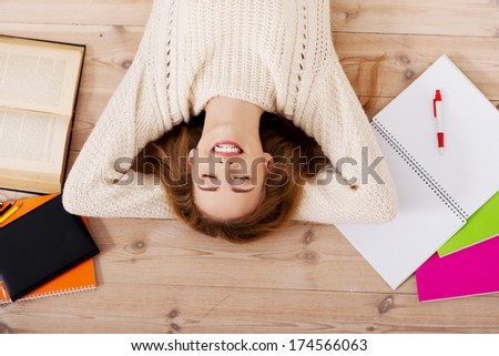 Young beautiful woman lying on the wooden floor with books. - stock photo