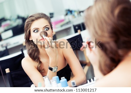 Young beautiful woman making faces and joking  with a make-up brush in front of a mirror - stock photo