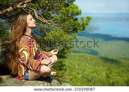 Young beautiful woman meditating at the mountains. healthy lifestyle. outdoors - stock photo