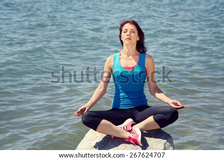 young beautiful woman meditating on the sea shore on a background of water - stock photo