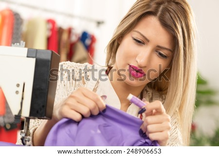 Young beautiful woman next to sewing machines, with one hand holding the material that sew, and in the other hand spool of thread. - stock photo