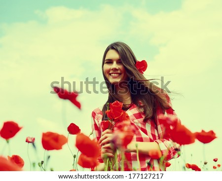Young beautiful woman on a poppy field, summer outdoor, toned - stock photo
