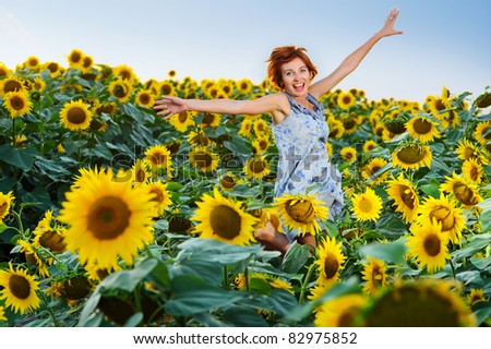 young beautiful woman on blooming sunflower field in summer - stock photo