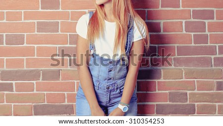 Young beautiful woman on red brick wall background. Hipster style. Toned image. Copyspace. - stock photo