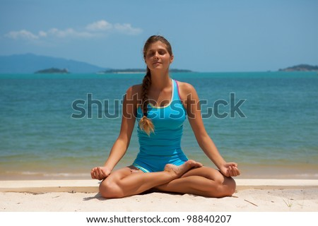 Young beautiful woman on the beach making yoga - stock photo