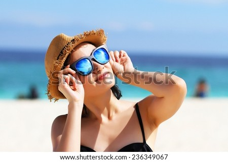 Young beautiful woman on the beach, Woman with sunglasses in bikini, Sunglasses reflects the sun.  - stock photo