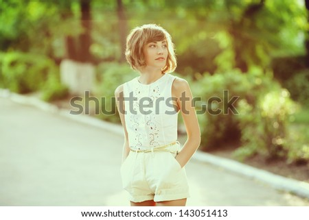 young beautiful woman outside in park, relaxing - stock photo