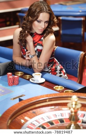 young beautiful woman playing in casino - stock photo