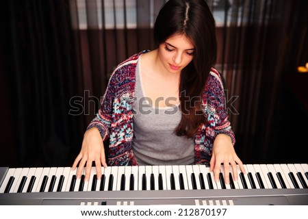 Young beautiful woman playing on piano at home - stock photo