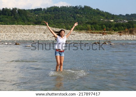 Young beautiful woman playing with water in cold mountain river - stock photo