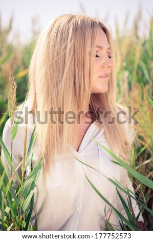 young beautiful woman poses in green thickets. fashion model - stock photo