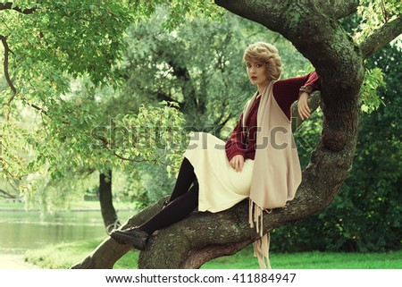 Young beautiful woman posing on a tree.  - stock photo