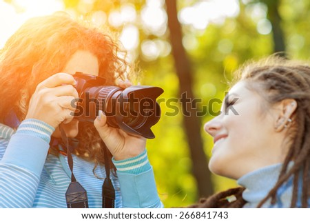Young beautiful woman posing woman-photographer on background summer green park. - stock photo