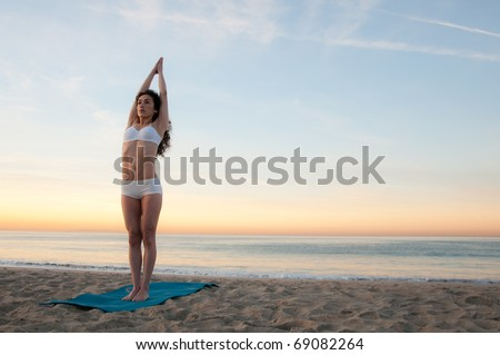 Young beautiful woman practicing yoga at sunrise on the beach by the ocean - stock photo