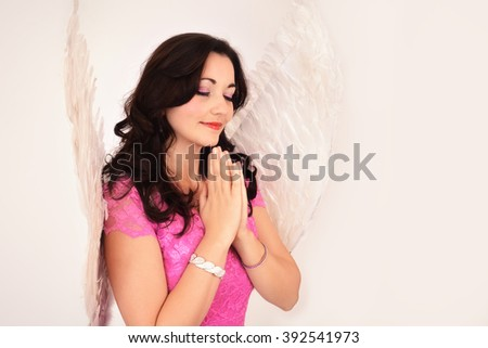 Young beautiful woman praying, dressed in angel costume - stock photo
