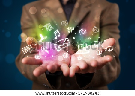 Young beautiful woman presenting colorful glowing social media icons - stock photo