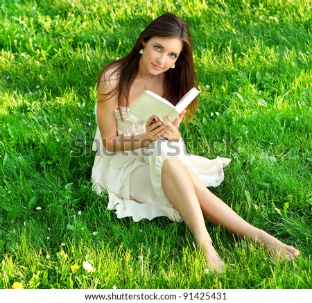 Young beautiful woman reading a book in nature - stock photo