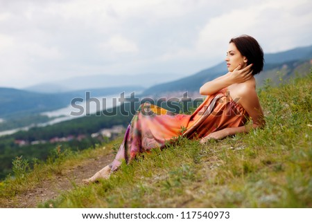 Young beautiful woman reading a book on the hill laying in the grass. - stock photo