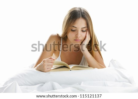 Young beautiful woman reading in bed - stock photo
