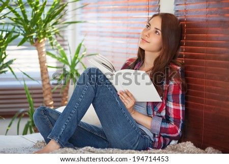 Young beautiful woman reading on the sofa - stock photo