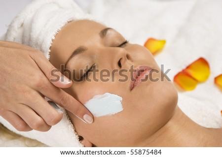 Young beautiful woman receiving a facial - stock photo