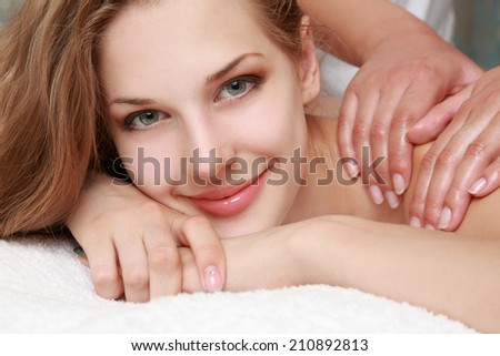 Young beautiful woman receiving back massage and spa treatment - stock photo