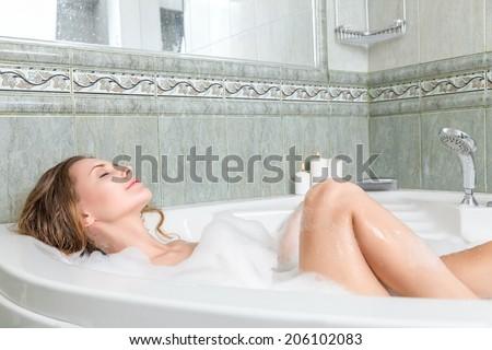 Young beautiful woman relaxing in a bath - stock photo