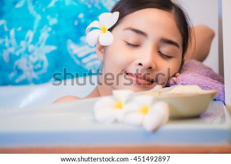 Young beautiful woman relaxing in a bath. Water treatment.Bathing woman relaxing in bath smiling relaxing with eyes closed. Multicultural Asian   - stock photo