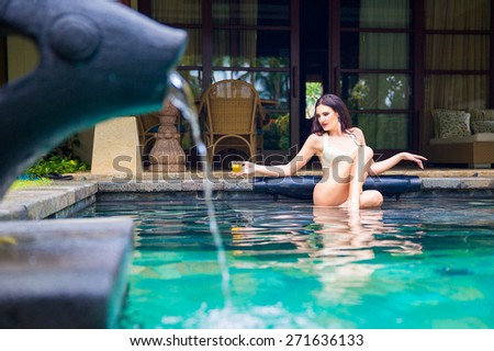 Young beautiful woman relaxing in a pool enjoying a cocktail at the hotel on a tropical island. Summer vacation concept. - stock photo