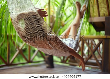 Young beautiful woman relaxing in hammock in a tropical resort.back view - stock photo