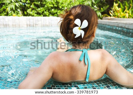 Young beautiful woman relaxing in spa pool. Relaxing serene woman at travel spa resort pool - stock photo