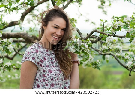 Young beautiful woman relaxing in the garden among blooming apple trees and smiling - stock photo
