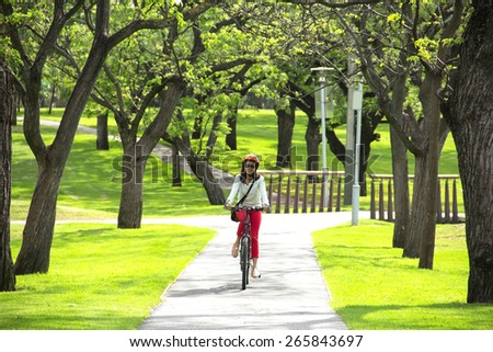 young beautiful woman riding a bicycle in city park. Active people. Outdoors - stock photo