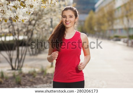 Young beautiful woman running in the city. - stock photo