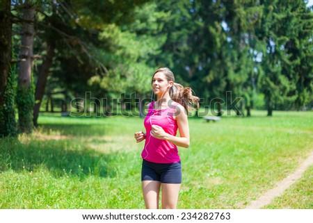 Young beautiful woman running outdoors - stock photo