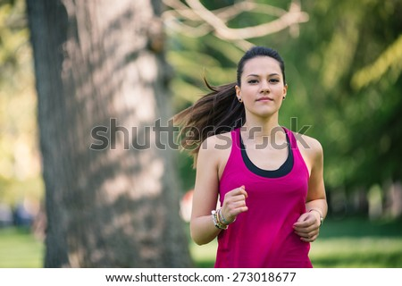 Young beautiful woman running outdoors in a park. - stock photo