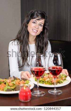 Young beautiful woman serving salad and red wine for anniversary dinner. - stock photo