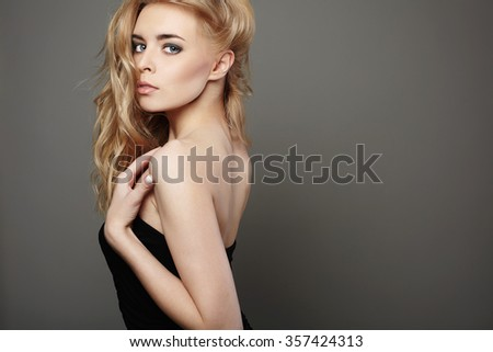 young beautiful woman.Sexy Blond girl. Gray Background.Curl Hairstyle - stock photo